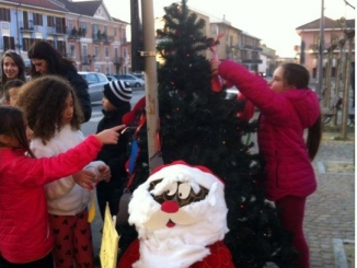 I bambini del gruppo Piedibus mentre allestivano l'albero, poi rubato da ignoti malfattori