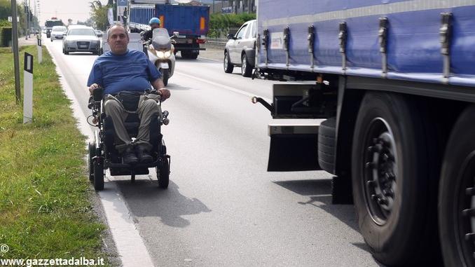 Ivo, in carrozzina sulla statale 231 senza marciapiede