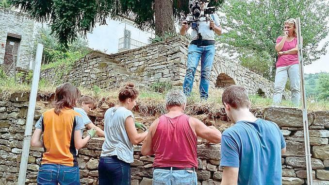 I volontari sistemano i vecchi muri in pietra