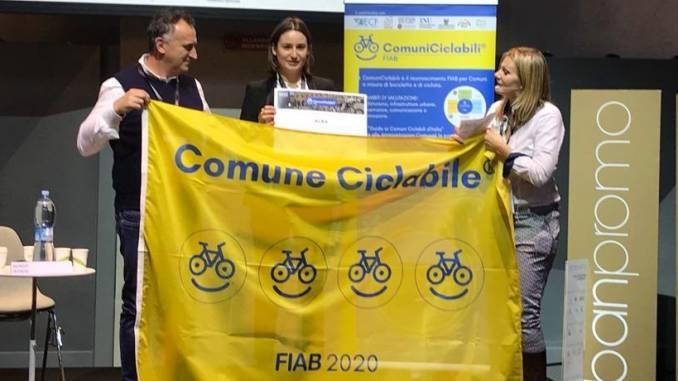 Alba riceve la bandiera giallo blu con quattro biciclette