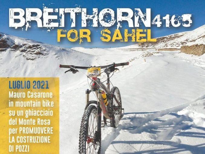 Mauro Casarone in mountain bike su un ghiacciaio del Monte Rosa per promuovere la costruzione di pozzi in Burkina Faso